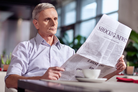 Whats new. Appealing handsome mature man sitting at the table while carrying newspaper and enjoying coffee Stock Photo