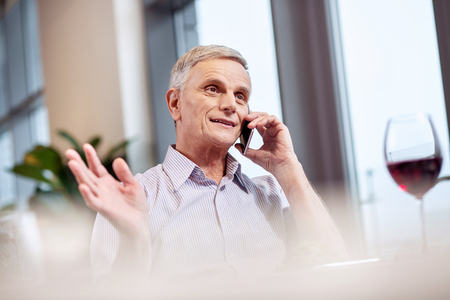 My opinion. Energetic vigorous mature man waving hand while talking on phone and looking straight
