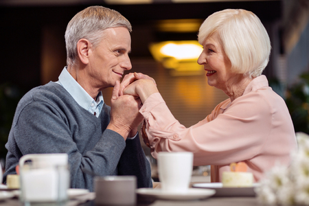Forever yours. Pleasant handsome mature man lipping wife hand and looking at her while smiling