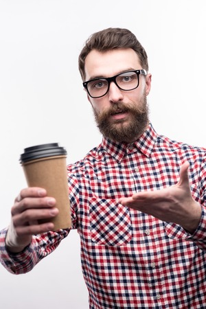 Taste it. Pleasant bearded man in eyeglasses offering a cup of coffee and pointing at the camera with his hand while posing isolated on a white background