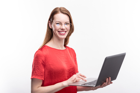 My device. Gorgeous ginger-haired young woman in a red blouse holding a laptop and posing with it against a white background while wearing eyeglasses