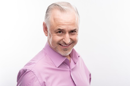 Playful mood. Pleasant grey-haired senior man in a lilac shirt standing-half turned and smiling at the camera cheekily while posing isolated on a white background
