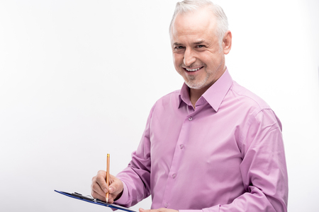 Office worker. Charming grey-haired man in a lilac shirt filling in a form on a sheet holder and smiling at the camera while posing isolated on a white background