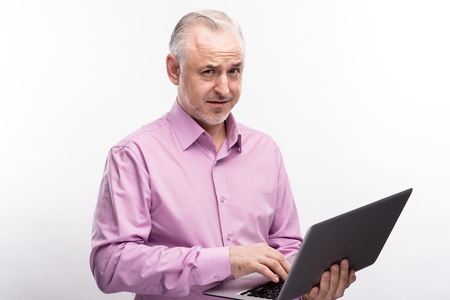 Do not think so. Grey-haired senior man holding a laptop and frowning with a doubting expression while posing isolated on a white background Stock Photo