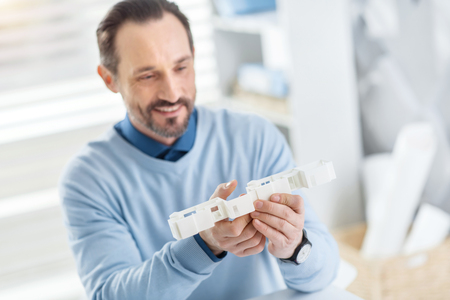 Working process. Handsome content dark-haired bearded man smiling and holding a model of a future house and looking at it Stock Photo