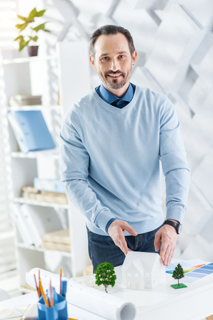 Great project. Handsome alert dark-haired bearded man smiling and touching a model of a future house while standing at the table