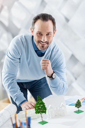 Inspiration. Good-looking joyful dark-haired bearded man smiling and constructing the model of a house while standing at the table