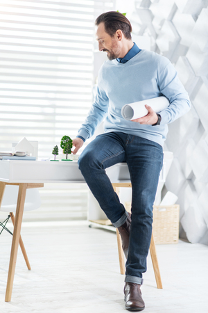 Constructing process. Handsome joyful dark-haired bearded man holding the drawing and smiling while sitting on the table and looking at the model of the house