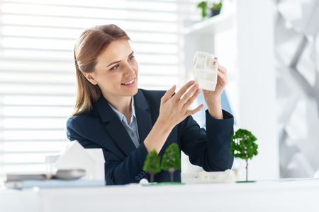 Young engineer. Pretty exuberant fair-haired young woman smiling and holding the models of the house while sitting at the table Stock Photo