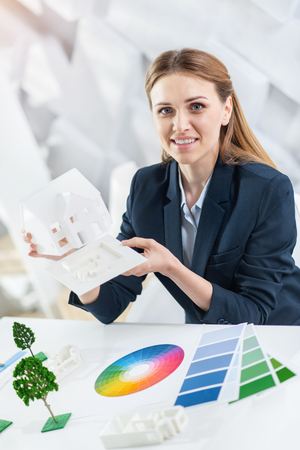 My lifestyle. Attractive cheerful fair-haired young woman smiling and holding a white little plastic model of the house while sitting at the table
