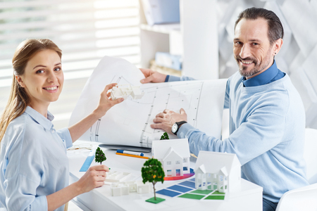 Happy co-workers. Good-looking exuberant bearded man smiling and holding a drawing and working with his colleague holding a miniature house while sitting at the table Stock Photo