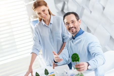 Happy workers. Pretty inspired fair-haired young woman smiling and working with her colleague holding a tree miniatures and she looking at it