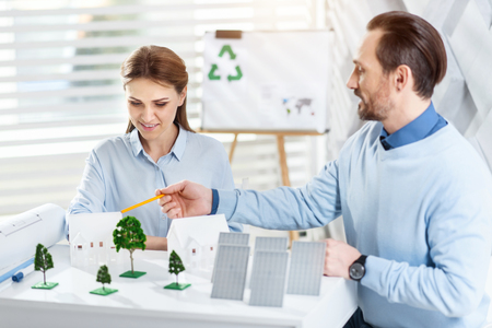 Eco-friendly. Attractive happy bearded man smiling and working with his colleague on an eco-friendly project while sitting at the table Stock Photo