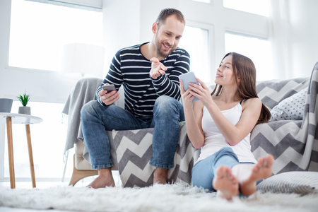 Have a look. Attractive joyful bearded young man sitting on the couch and holding his phone and his woman sitting on the floor and showing him some pictures on her phone Stock Photo