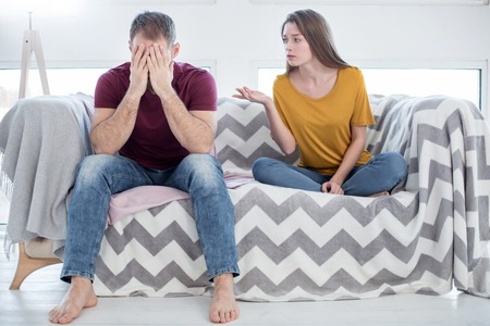 Cheating on her. Attractive heart-broken young woman talking to her man about his unfaithfulness and he closing his face while sitting on the couch Stock Photo