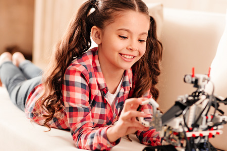 Selective focus on a radiant girl with ponytails smiling cheerfully while relaxing on a sofa and playing with an impressive robot toy. Stock Photo