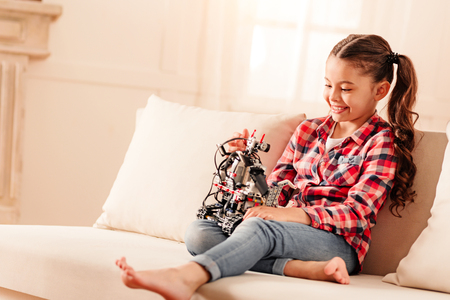 Extremely happy preteen child sitting on a sofa and smiling cheerfully while playing with her new robotic machine at home.