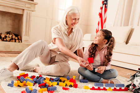 Adorable senior lady and her preteen grandchild sitting on the floor and smiling cheerfully while looking at each other and playing with plastic building blocks.