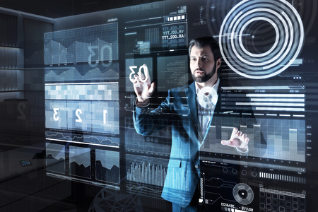 Smart experienced qualified programmer looking careful while standing alone in a dark office and looking at the big numbers on a futuristic transparent screen