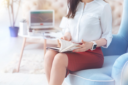 Scaled up look on a career woman working in an office and searching for the notes written in her notebook. Stock Photo