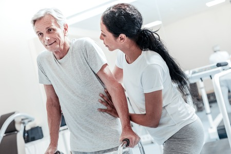 Joyful concentrated old grey-haired man exercising while a pretty dark-haired afro-american woman helping and holding him Stock Photo