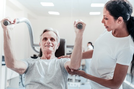 Exuberant energetic old grey-haired man exercising on a training device and a pretty young dark-haired female trainer standing near him and touching his hand Stock Photo