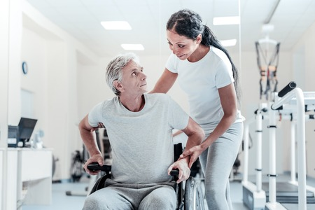 Concentrated old grey-haired man sitting in a wheelchair and an attractive young dark-haired woman standing near him and smiling while they looking at each other Imagens