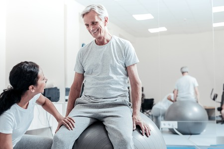 Cheerful smiling old grey-haired man sitting on a ball for exercises and a young dark-haired afro-american woman sitting near him and touching his leg and they looking at each other