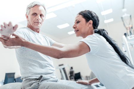 Concentrated old grey-haired man sitting on a ball for exercises and a beautiful young dark-haired afro-american woman helping him to train his arms and touching his arm and leg Imagens