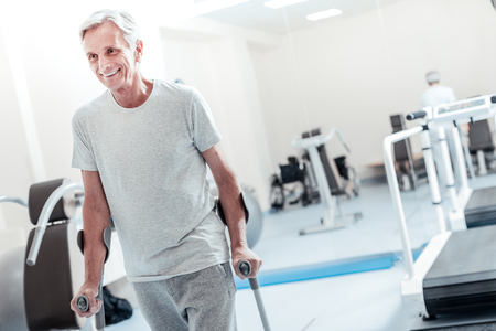 Alert old grey-haired man smiling and standing while holding and standing with the help of walking sticks