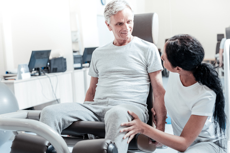 Cheerful old crippled grey-haired man smiling and exercising on a training device while a young dark-haired female trainer sitting near him and they looking at each other Banco de Imagens