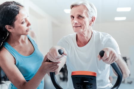 Smiling old wrinkled grey-haired man exercising on a training device while a beautiful young dark-haired female trainer standing near him and looking at him seriously