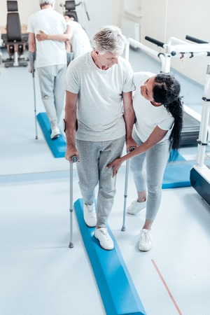 Concentrated aged grey-haired man walking with his walking sticks and looking at his young dark-haired afro-american female trainer helping him walk in the gym Stock Photo