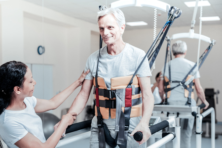 Exuberant vigorous old grey-haired man smiling and exercising on a training device and a smiling dark-haired woman standing near him and touching his hand Stock Photo