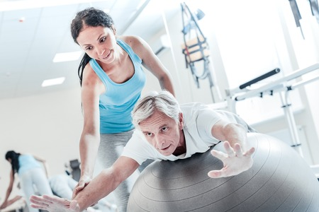 Concentrated old grey-haired crippled man lying on a big ball and training his muscles while an alert young dark-haired female trainer smiling and holding him Stock Photo