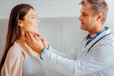 Side view on a young woman smiling while visiting her doctor and checking her health. Stock Photo - 95986634
