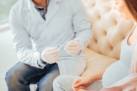 Careful qualified concentrated medic in a rubber gloves sitting in the room on the sofa and holding the syringe and preparing for injection. Stock Photo