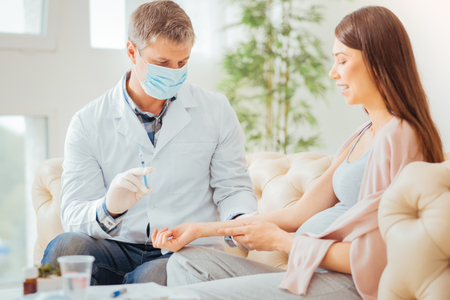 Calm responsible concentrated doctor sitting near a woman preparing for injection and holding the syringe. Stock Photo