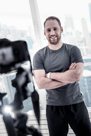 Positive inspired male blogger staying near window while recording video and promoting sport