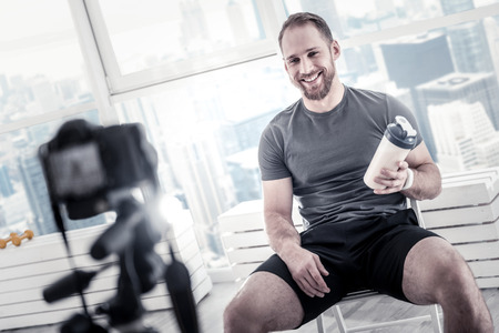 Cheerful male blogger carrying bottle while grinning and sitting on chair