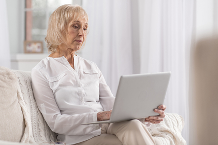 Focused serious mature woman typing laptop while thinking and staring at screen