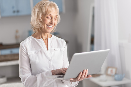 Joyful beautiful mature woman laughing while posing on the blurred background and working with laptop Stock Photo