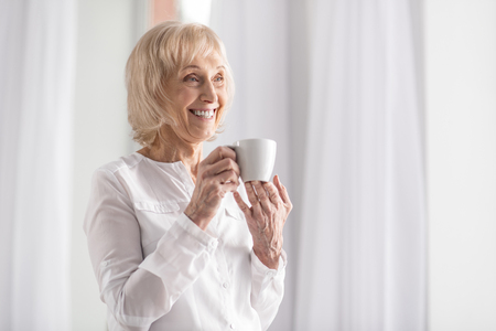 Happy vigorous mature woman laughing while standing on the light background and drinking coffee