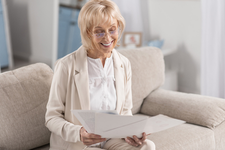 Joyful glad mature businesswoman wearing glasses while examining papers and grinning