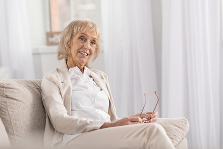 Merry jolly mature woman posing on couch while thinking and relaxing