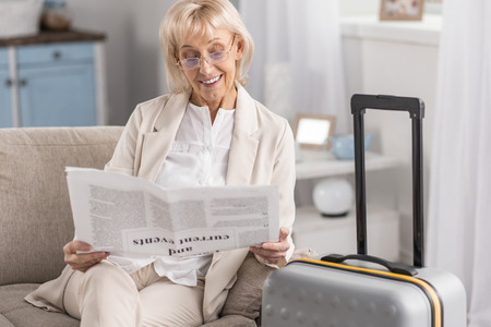 Optimistic happy mature woman sitting near suitcase while holding newspaper and wearing glasses Фото со стока - 95998824