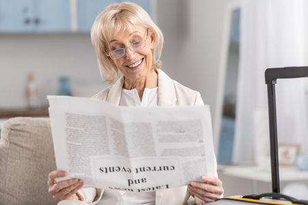Confident attractive mature woman smiling while examining article and putting on glasses