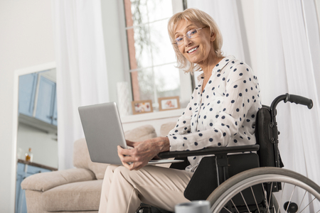 Pleasant disabled mature woman sitting in wheelchair while holding laptop and smiling to camera Stock Photo