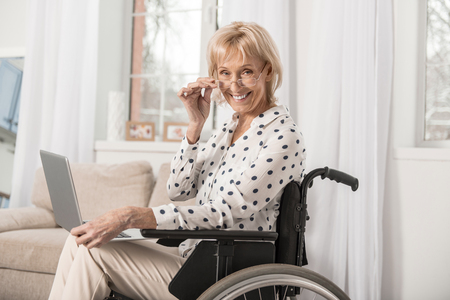 Disabled optimistic mature woman grinning in wheelchair while touching glasses and staring at camera