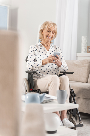 Handicapped optimistic mature woman using phone in wheelchair while smiling and looking down